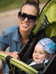 Cute boy in stroller beside mom